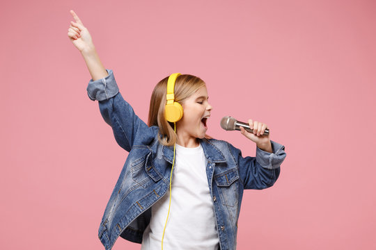 Cute little kid girl 12-13 years old isolated on pastel pink background. Childhood lifestyle concept. Mock up copy space. Listen music with headphones sing song in microphone pointing index finger up.