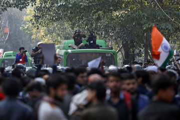 Police officials sitting atop a bus take videos of demonstrators during a protest against a citizenship law, in New Delhi