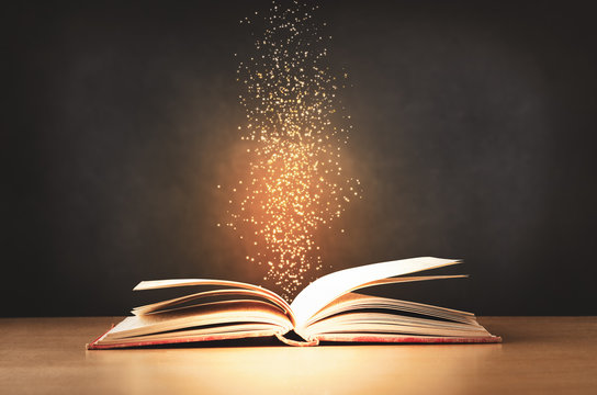 Old Book Opened on Desk with Sparkling stars Rising Upwards