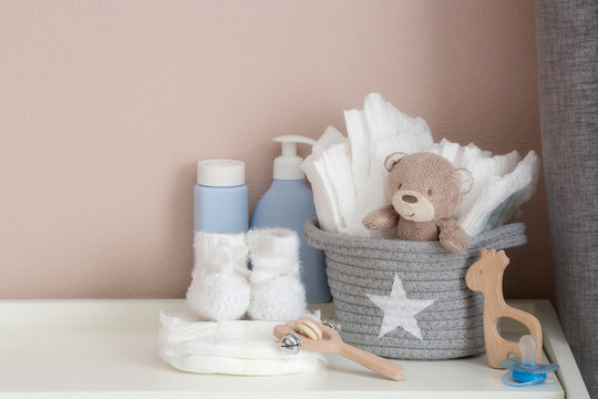 A stack of diapers, booties and baby accessories on a changing table. Copy space for text.