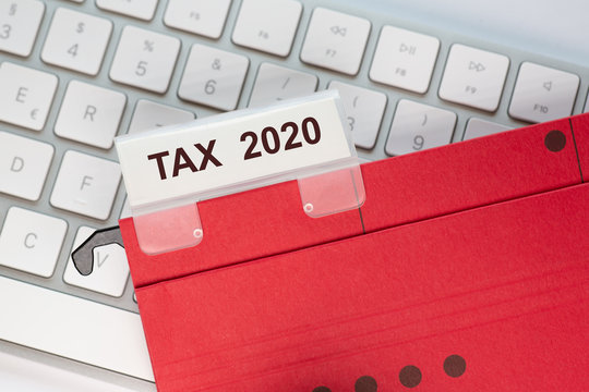 red hanging folder on a keyboard has a tab with the words TAX 2020  on it