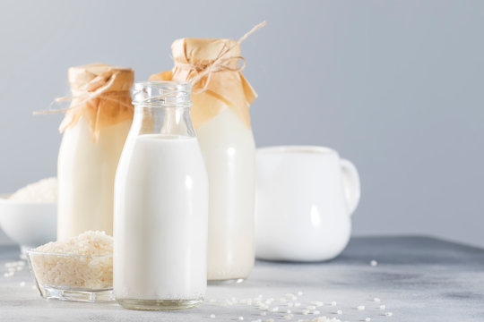 Vegan rice plant based milk in bottles, closeup, gray background. Non dairy alternative milk. Healthy vegetarian food and drink concept. Copy space