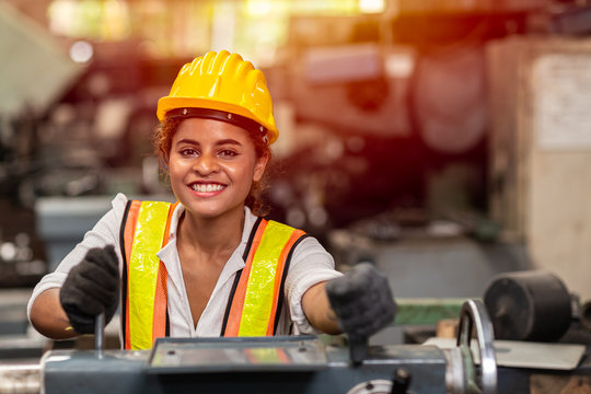 Girl teen worker with safety helmet happy smiling working labor in industry factory with steel machine.