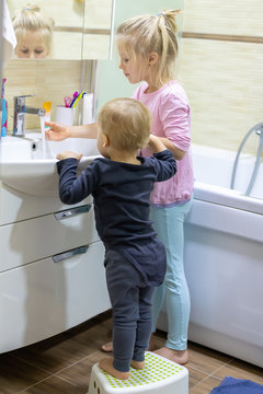 Two cute adorable blond caucasian siblings washing face and cleaning tooth with toothbrush at bathroom at home in morning. Little children brother and sister do daily higyene health care. Funny kids