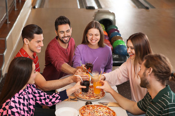 Group of friends with drinks and pizza in bowling club