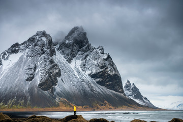 Man in a yellow jacket on the background of Vestrahorn Mountain. Iceland