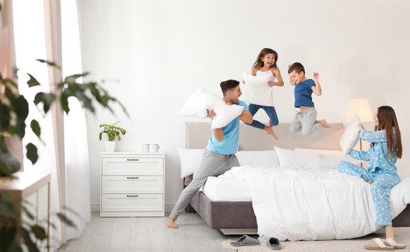 Happy family having pillow fight in bedroom