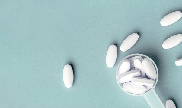 White pills in dosage spoon for drugs on a blue background, close-up