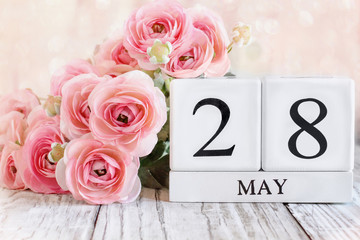 White wood calendar blocks with the date May 28th and pink ranunculus flowers over a wooden table for National Memorial Day. Selective focus with blurred background.