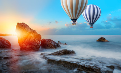 Wall Mural - Hot air balloon over the sea at amazing sunset - Long exposure image of Dramatic sky and seascape with rock