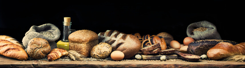 Banner with different types of bread and rolls, eggs, wheat, rye, sunflower oil and ears. Toned. Panorama of five photos.