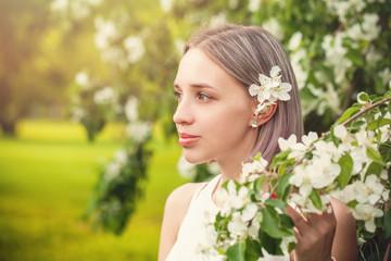 Pretty girl in spring flowers garden