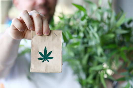 Male hand hold paper packet with marijuana symbol closeup background. Online shopping sativa concept