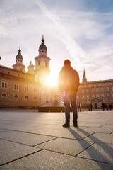 Tourism in Salzburg: Young man is standing on the cathedral square and watching the sundown