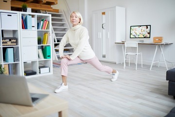 Full length portrait of active mature woman stretching legs during workout at home, copy space