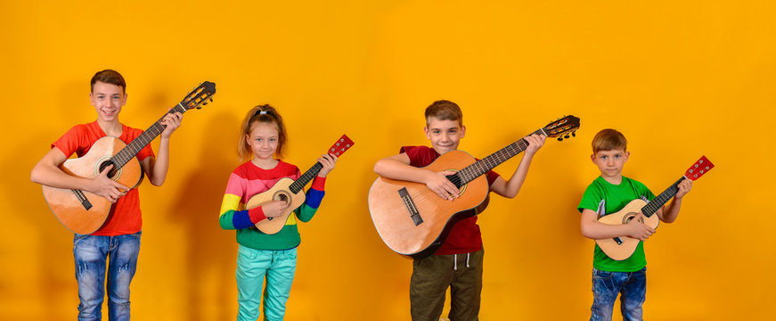 Four children with acoustic guitars in bright and colorful clothes stand in a row on a yellow background.