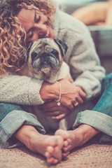 Concept of love and friendship with cheerful happy adult woman and old funny pug dog looking at the camera - home life scene with dog best friend forever