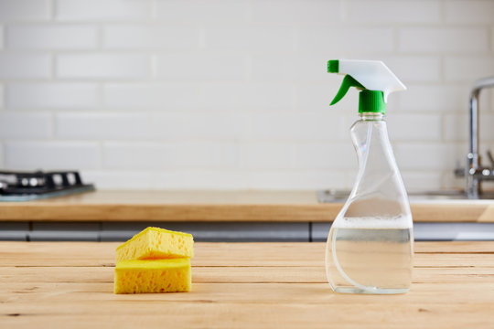 yellow sponge and plastic bottle with liquid on wooden table, kitchen background