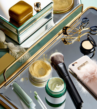 Overhead view of makeup and mobile phone on gold mirrored tray