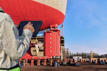 worker in Shipyard Stern ship propeller, rudder and shafting port controller, surveyor, inspecting the final repairing of propeller on dry dock. Wall mural