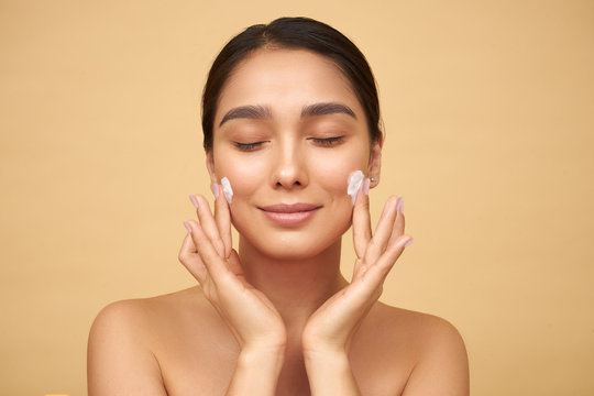 Young girl with closed eyes with clean skin puts cream on her face with hands on a yellow background