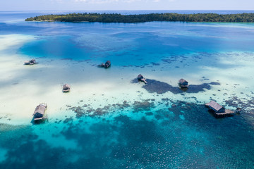 Fishing shacks are built on a remote reef in the Molucca Sea, Indonesia. This tropical region is known as the heart of the Coral Triangle due to its incredible marine biodiversity.