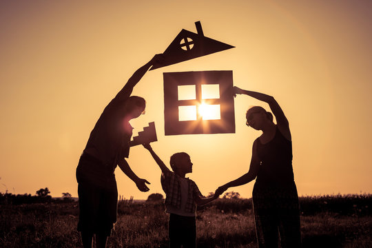 Happy family standing on the field at the sunset time. They build a house.