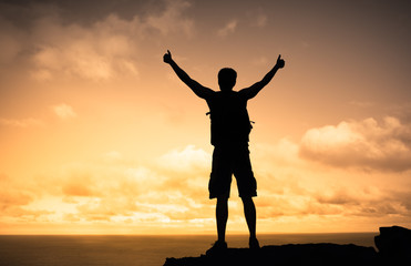 Strong male mountain climber with thumbs up celebrating success and life