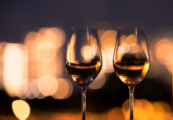 Wall Mural - closeup of empty wine glasses on restaurant table with city night views.