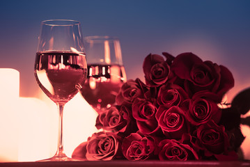 Wall Mural - two glasses of red wine and roses.Romantic date night setting