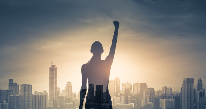 confident young woman with fist in the air facing the city. People power and strong young woman concept