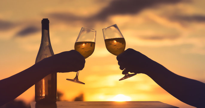 People enjoying wine at sunset. Cheers and romantic celebration concept.