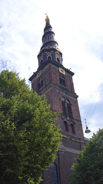 COPENHAGEN, DENMARK - JUL 06th, 2015: Our Saviour's Vor Frelsers Kirke - one of Denmark's most famous churches. Serpentine spire was inaugurated in 1752 - a popular pastime to climb 400 steps to top