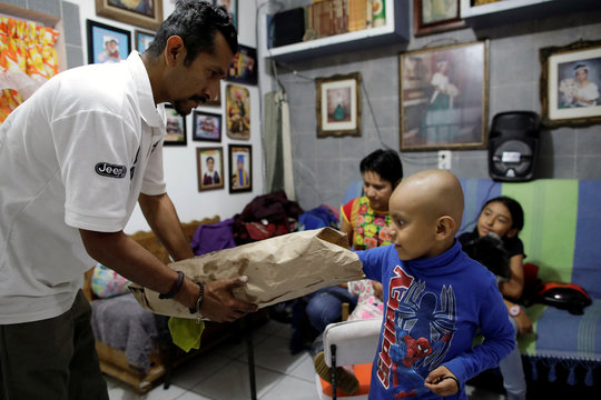 Hermes Soto takes a cookie as his father, Armando Soto, holds a bag in his house in Mexico City