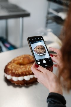 Vertical shot of a woman taking a picture of a cake with her smartphone