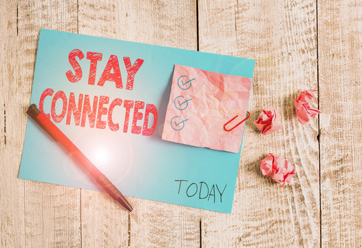 Conceptual hand writing showing Stay Connected. Concept meaning To keep communicating on each other To retain in touch Wrinkle paper and cardboard placed above wooden background