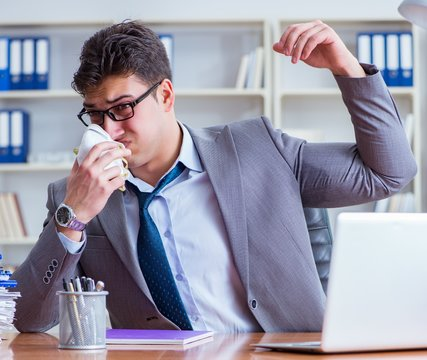Businessman sweating excessively smelling bad in office at workp