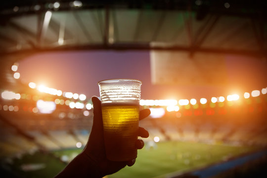 Disposable glass with beer. Soccer stadium on the background