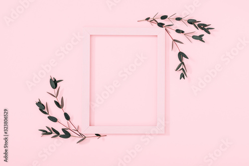Minimal composition of eucalyptus. Photo frame, eucalyptus branches, leaves on pastel pink background. Valentines Day, Easter, Happy Women's Day, Mother's day. Flat lay, top view, copy space