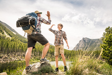 Father and son balance and stand on rock triumphantly and high fiving while hiking in the mountains. Greenough Lake,  Montana, USA
