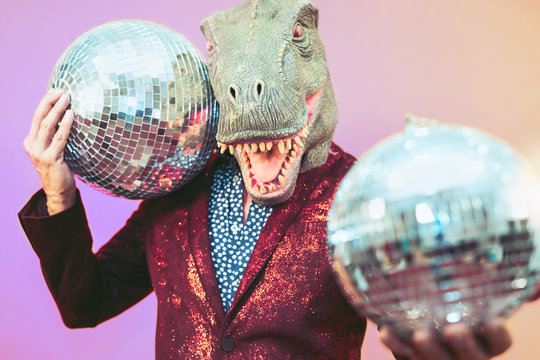 Senior man having fun wearing t-rex mask in discotheque - Elegant dinosaur masquerade male celebrating carnival party inside disco club - Funny absurd holidays and crazy people humor lifestyle concept
