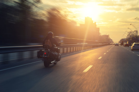 Silhouette of biker riding black chopper motorcycle on city street highway road and sunset bright dramatic sky on background. Alone biker dryving cycle. Cruise adventure and travel concept. Lifestyle