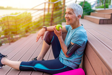 Foto op Plexiglas Kruidenierswinkel Portrait of a beautiful older woman with green healthy food after workout. Portrait of fit mature woman smiling while holding an apple and bottle of water. Sporty senior woman