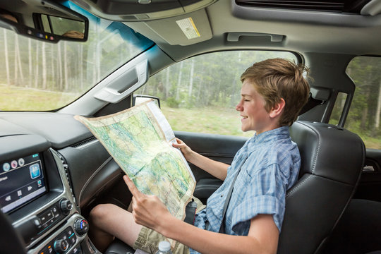 Boy reading a map in car while father is driving. Montana, USA