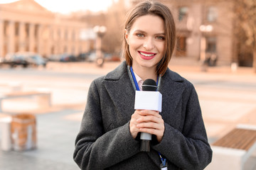 Beautiful journalist with microphone outdoors