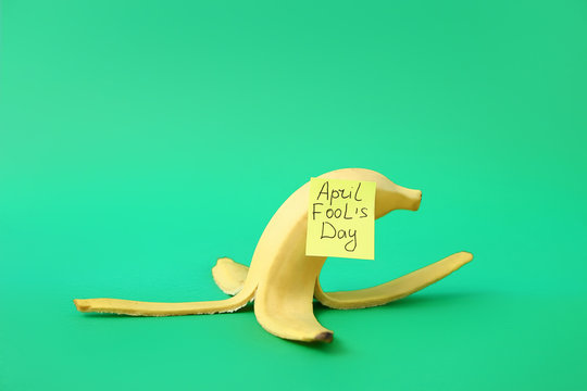 Banana peel on color background. April Fool's Day prank