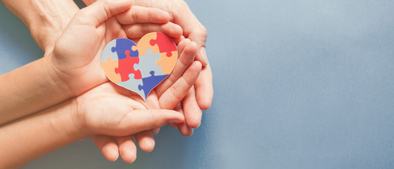 Adult and chiild hands holding jigsaw puzzle heart shape, Autism awareness,Autism spectrum disorder family support concept, World Autism Awareness Day
