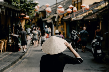 Tourist woman wearing vietnam hat or Non La and sightseeing at Heritage village in Hoi An city in Vietnam.