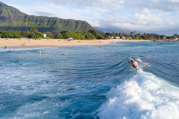 Wall Mural - Surfers in the ocean on Makaha surf spot, west coast of Oahu, Hawaii