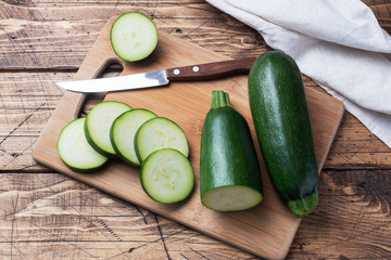 Fresh green zucchini cut into slices on a cutting Board. Wooden rustic table background.
